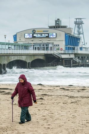 Pensioner walking across the beach near Bournemouth Pier in high winds and persistent rain. Bournemouth Beach Photography Dorset Out Walking