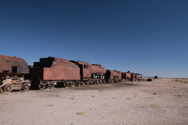 Abandoned Train At Desert Against Clear Blue Sky