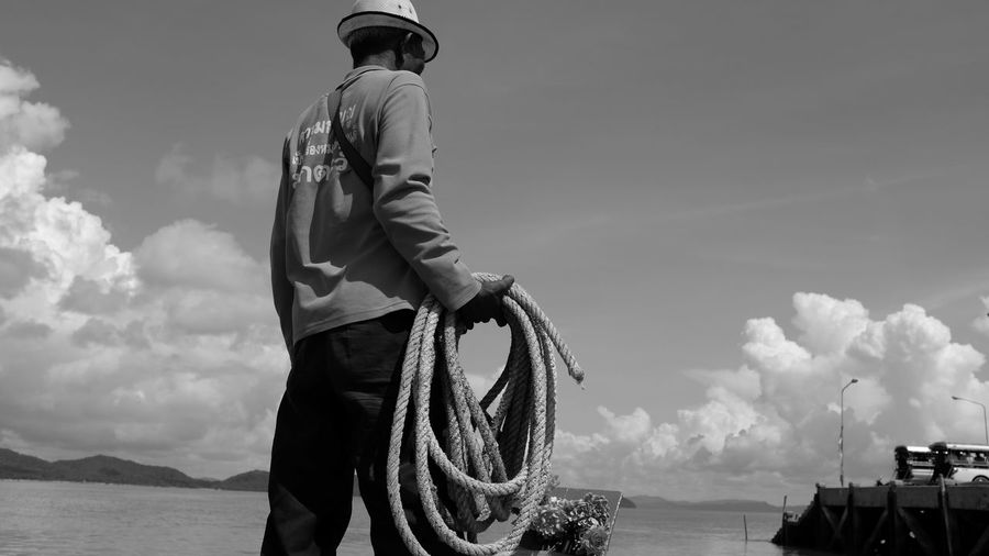Rear view of man with rope standing in front of sea