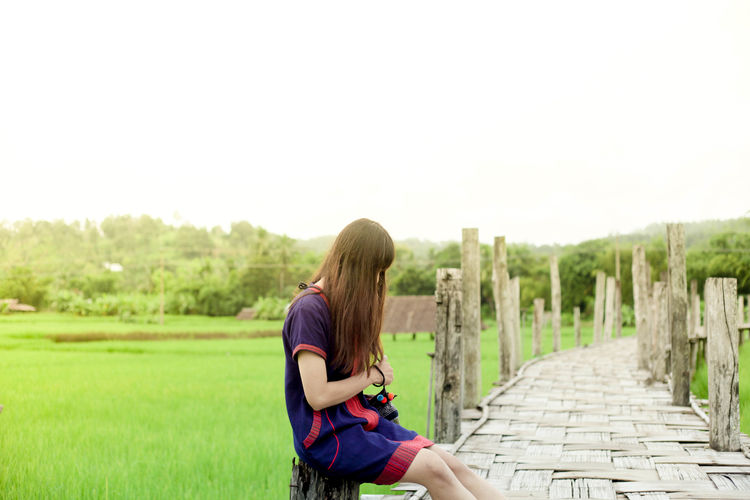Woman Sitting On Wooden Posts Against Clear Sky