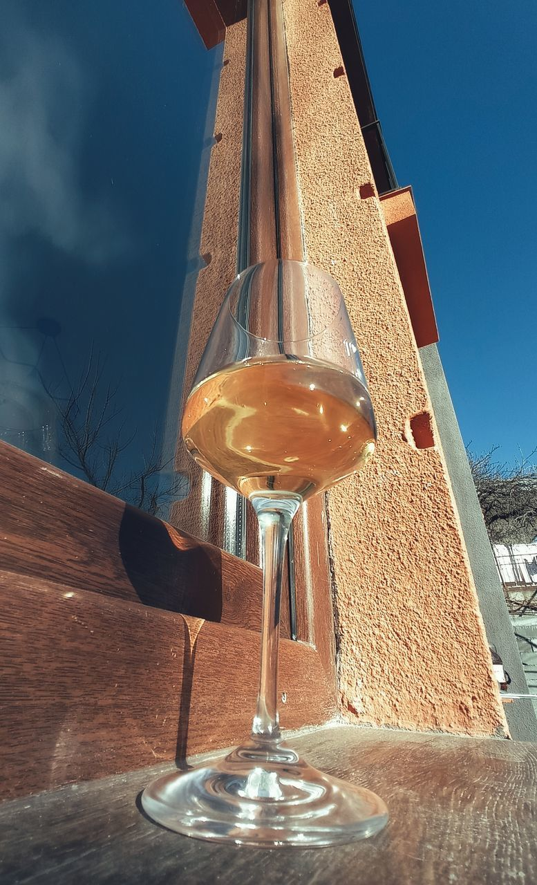 LOW ANGLE VIEW OF GLASS ON TABLE AGAINST SKY