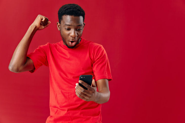 Young man using mobile phone against red background
