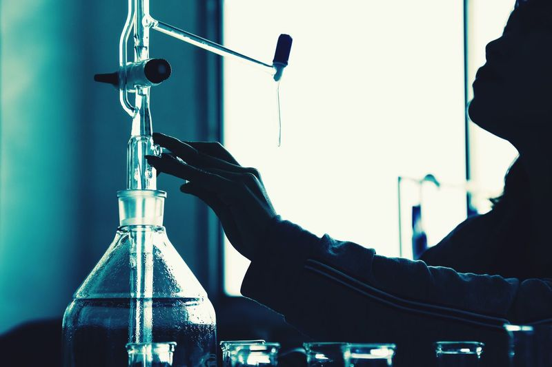 Chemistry student girl One Person Human Hand Indoors  Bottle Human Body Part Holding Men Study Occupation Women Adult People Close-up Day Adults Only Lab Flask Science Research Liquid Pipette Test Tube Industry University