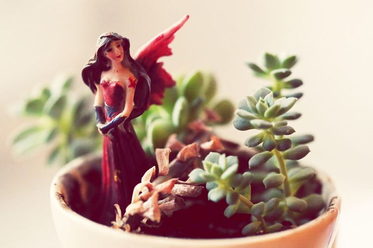 Close-Up Of Figurine On Potted Plant At Home