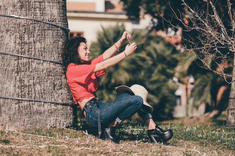Girl doing a selfie in the park sitting near a tree EyEmNewHere Hat Jeans Playing Games Red Casual Clothing Day Emotion Happiness Nature People Phone Plant Playing With Phone Portrait Red Shirt Selfie Sitting Tree Women The Portraitist - 2018 EyeEm Awards