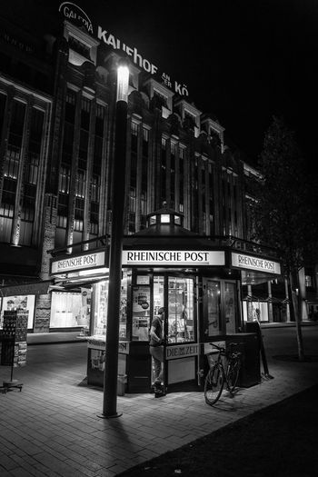 Packing Up Real People City Street Building Architecture Night Illuminated Text Western Script Street Light People Nightphotography Night Lights Newspaper Germany Deutschland Düsseldorf Monochrome Blackandwhite Black And White Canon Canonphotography Nighttime Europe EyeEmNewHere
