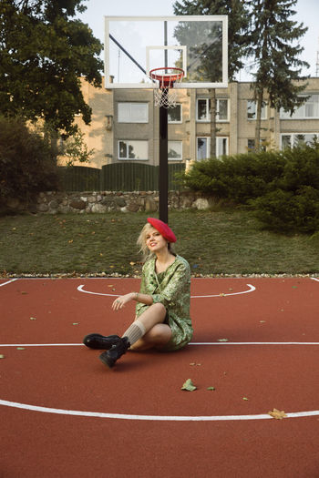 Full length of woman sitting at basketball court