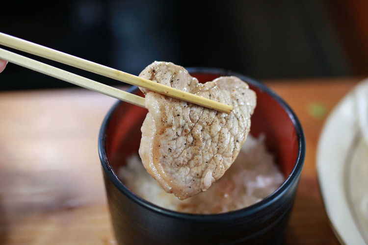 Close-Up Of Chopsticks Holding Meat