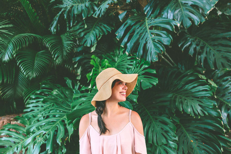 a woman in a sun hat, standing in front of tropical plants, smiling off camera Sun Hat Outdoors Beautiful Woman Standing Smiling Women Real People Young Adult Tropical Plants Portrait Woman