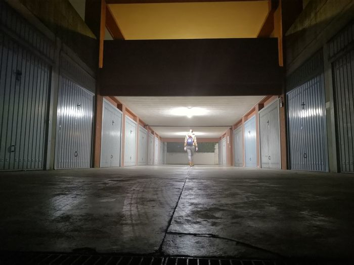 Rear view of woman walking in illuminated building