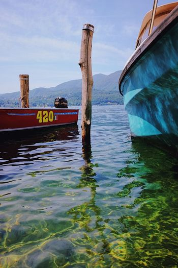 Close-up of boat in harbor, Italy. Beauty In Nature Blue Close-up Day Fishing Boat Harbor Longtail Boat Mode Of Transport Mountain Nature Nautical Vessel No People Outdoors Reflections Ripples Scenics Sky Speed Boat Transportation Water