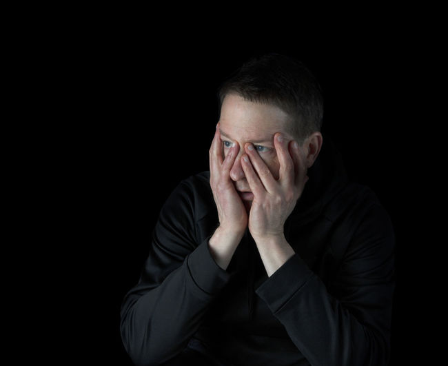 Midsection of man covering face against black background