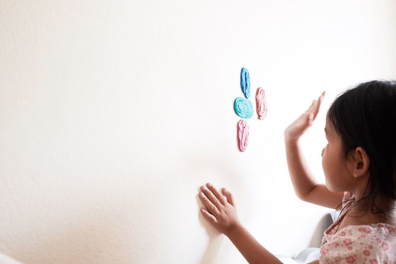 Side View Of Girl Sticking Clay On Wall