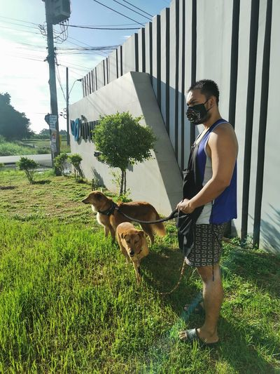 Man with dog standing by plants