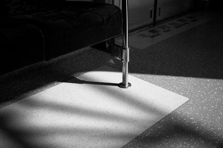 Close-up of metallic stand on tiled floor in train