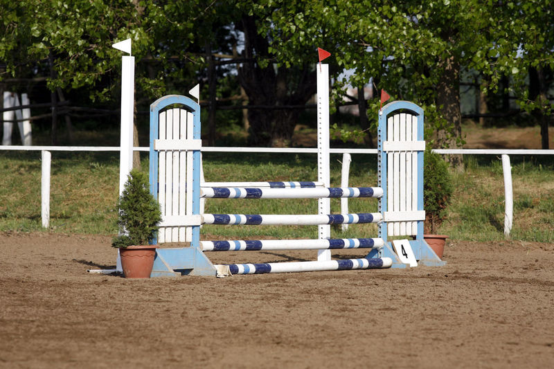 Colorful photo of equestrian obstacles. Barriers at horse jumping event competition No People Absence Empty Outdoors Land In A Row Park White Color Barrier Boundary Fence Sand Sunlight Wood - Material Barrier Gate, Horse Photography  Horses Of Eyeem Riders Cup Competition Time  Event Photography Hurdle Practice Open Air Riding Hall Beautiful Day Skills Training