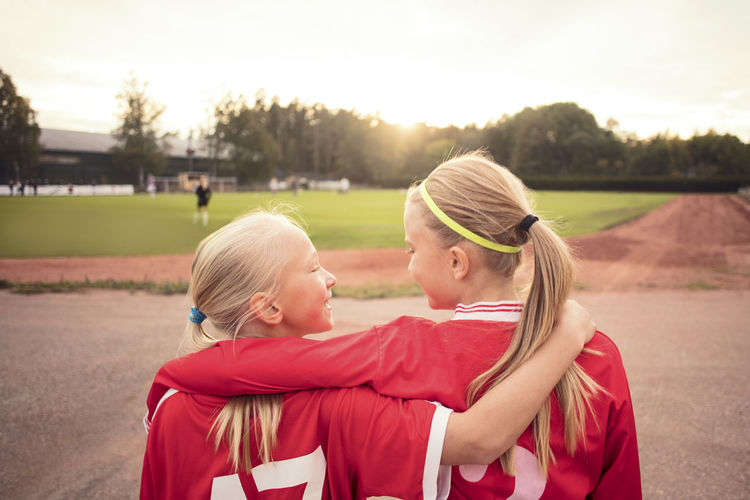 Rear view of mother and girl on field