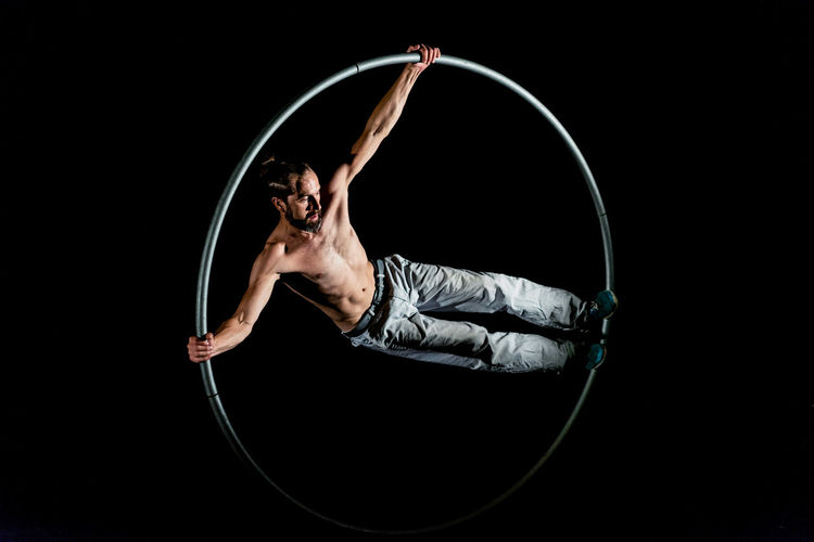 Circus Adult Arms Raised Balance Black Background Exercising Flexibility Front View Healthy Lifestyle Human Arm Indoors  Lifestyles One Person Performance Plastic Hoop Skill  Sport Strength Studio Shot Vitality Young Adult