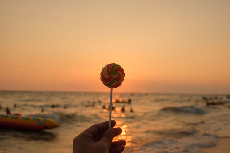 Taffy Beach Beauty In Nature Body Part Candy Finger Hand Holding Horizon Horizon Over Water Human Body Part Human Hand Land Leisure Activity Lifestyles Lolipop Nature One Person Outdoors Real People Sea Sky Sunset Water