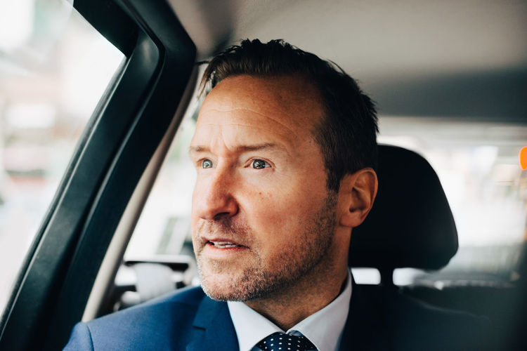 Mature businessman looking away while sitting taxi in city