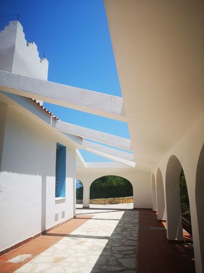 Corridor of building against blue sky