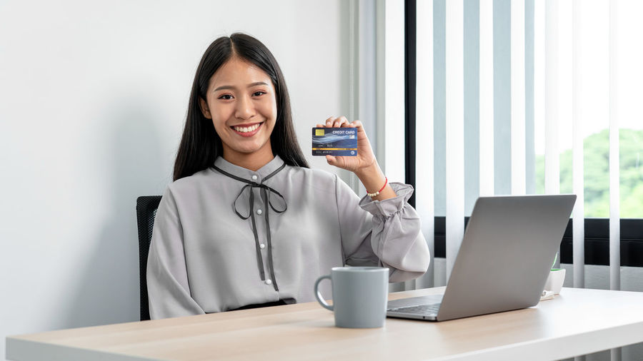 Portrait of smiling young woman using phone on table