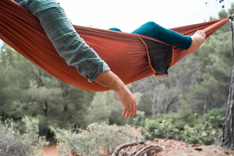 Man relaxing on hammock against trees
