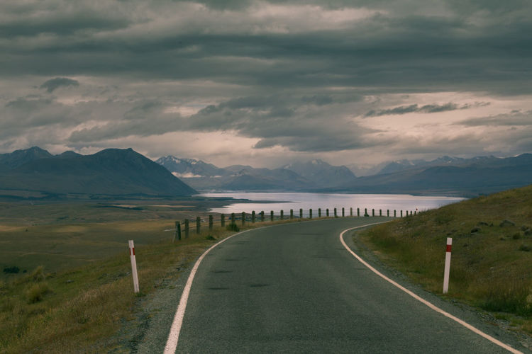 Road with a corner to the tekapo lake in new zealand with a cloudy sky