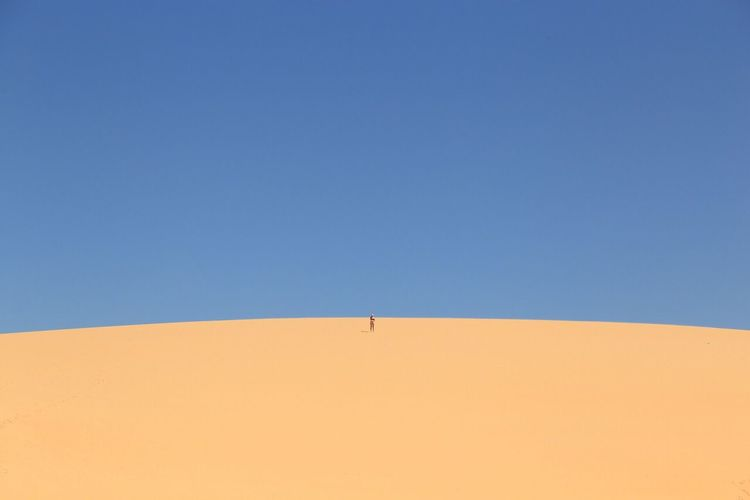 Mid Distance View Of Person Standing In Desert Against Clear Blue Sky
