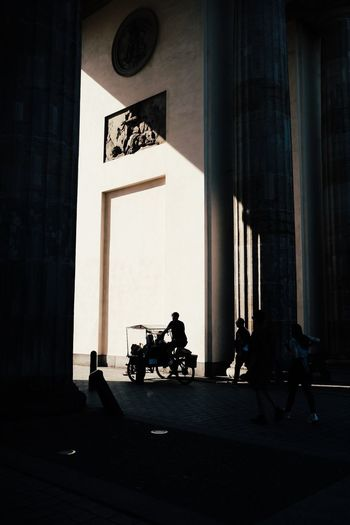 Silhouette people walking by building in city