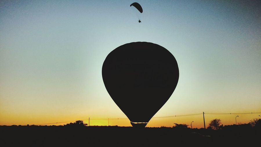 Silhouette hot air balloons against sky during sunset