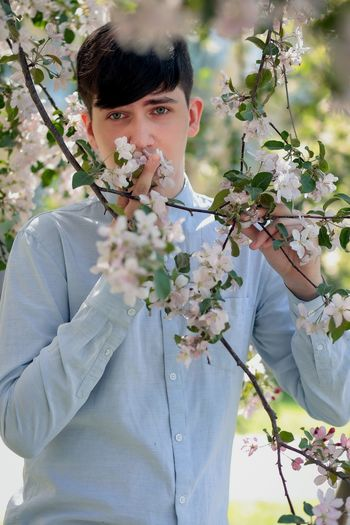 Portrait of young man holding flowering plant