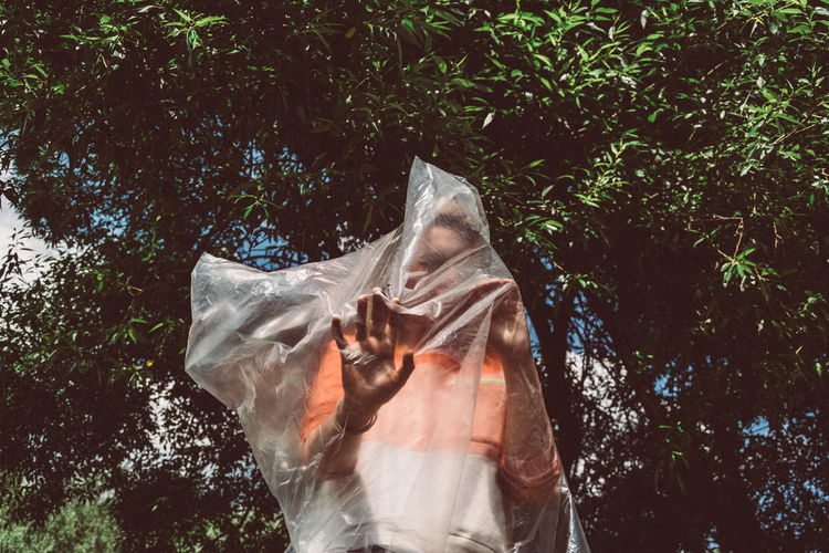 Low Angle View Of Woman Wrapped In Plastic While Standing Against Trees