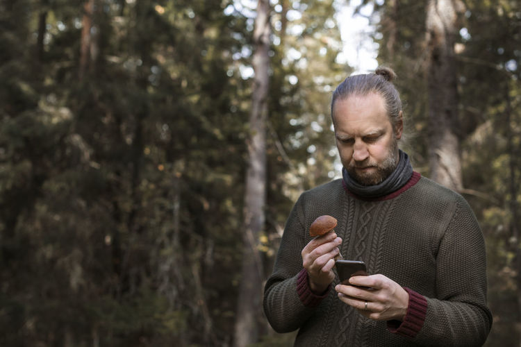 Man holding mobile phone in forest