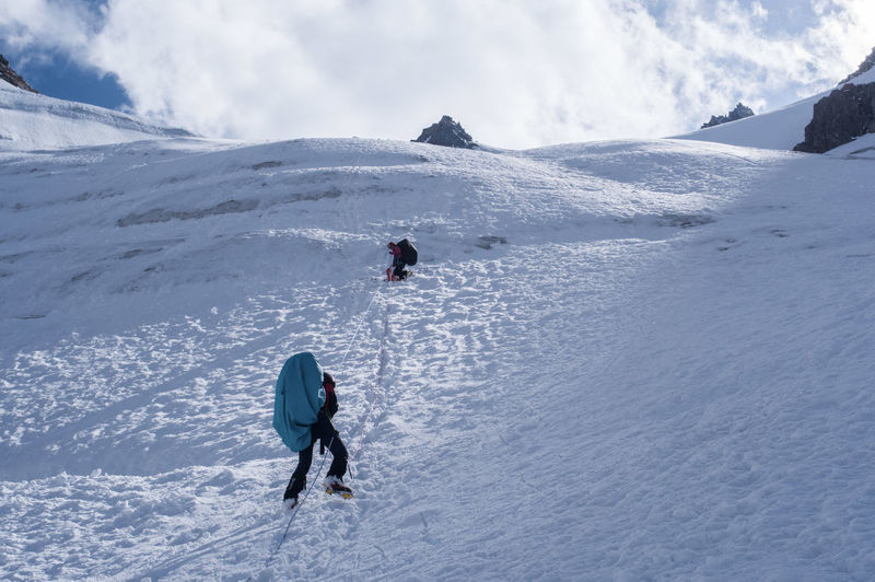 People hiking on snowcapped mountain during winter