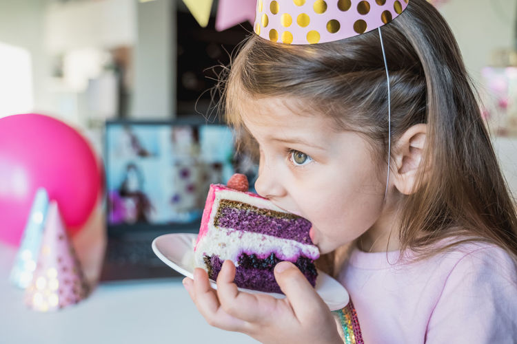 Cute girl eating cake in plate