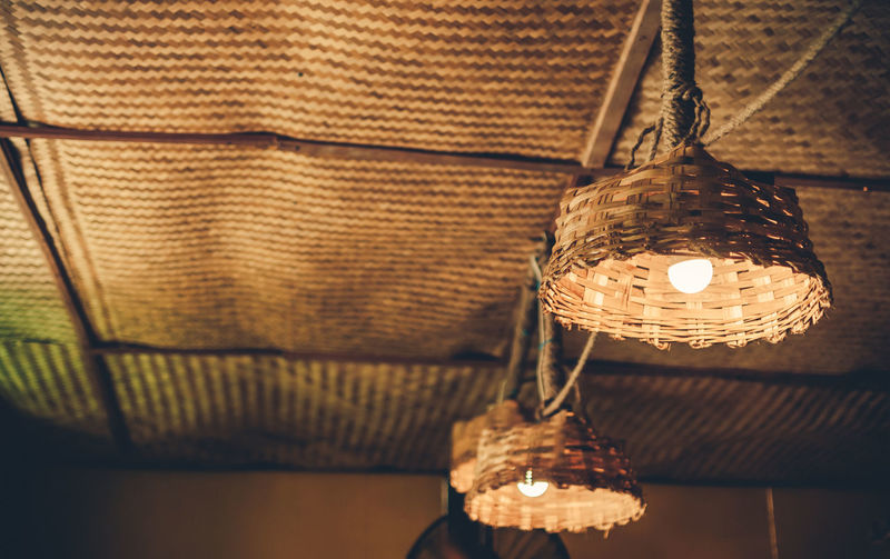 Low Angle View Of Illuminated Wicker Pendant Lights At Cafe