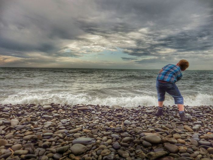 Boy bending at beach against cloudy sky