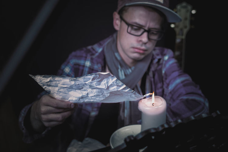 Close-up of young man burning foil on candle