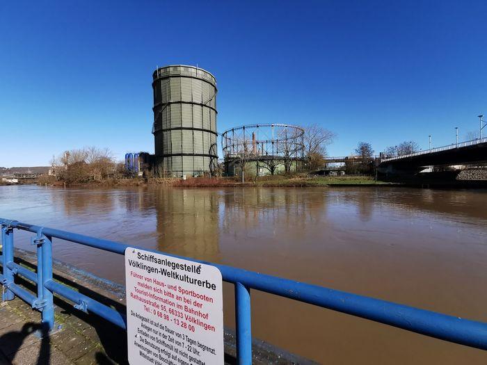 Water drops on metal railing against blue sky