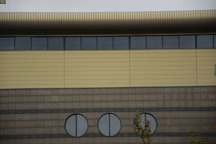Windows in the facade of the building Patern Pieces Tree Architecture Building Building Exterior Built Structure Circle Windows Corrugated Day Design Modern No People Outdoors Pattern Shape Technology Wall - Building Feature Window Yellow