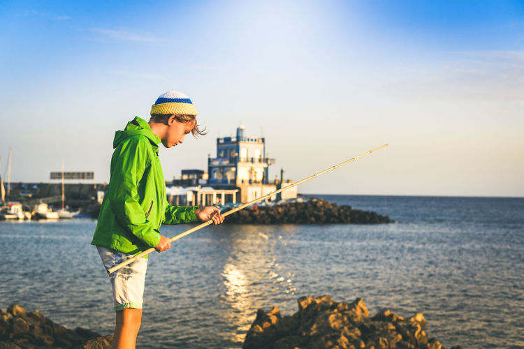 Side view of boy fishing at beach