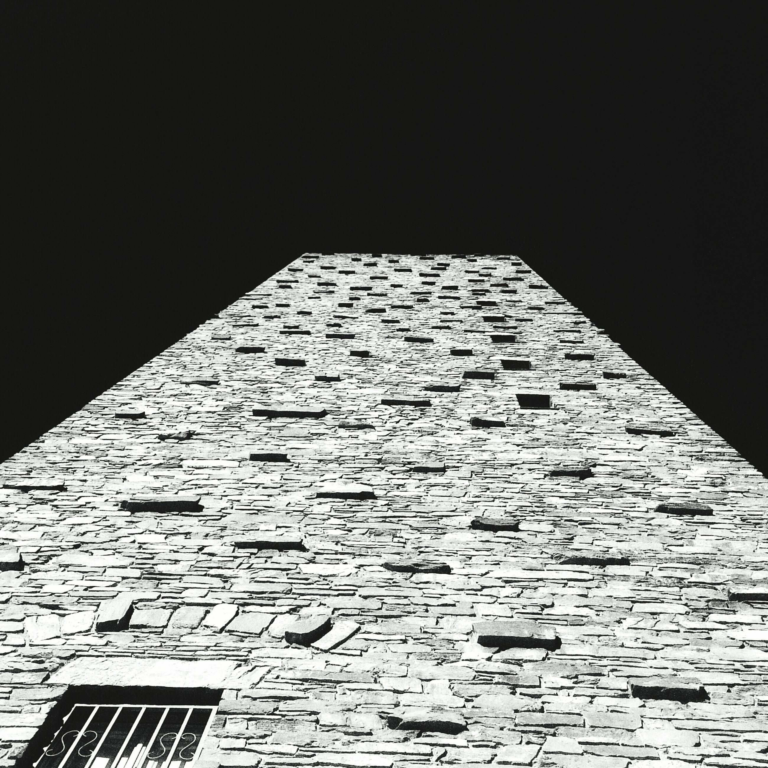 architecture, built structure, building exterior, low angle view, pattern, wall - building feature, clear sky, no people, day, outdoors, copy space, building, sunlight, shadow, brick wall, design, window, textured, geometric shape, wall