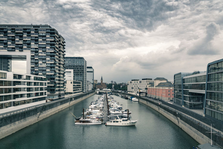 Boats in rhine river by kranhaus against cloudy sky