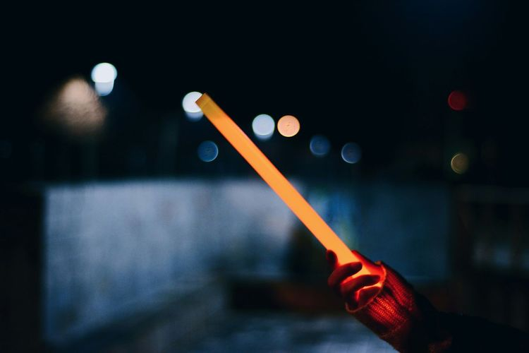 Cropped Hand Holding Laser Sword At Night