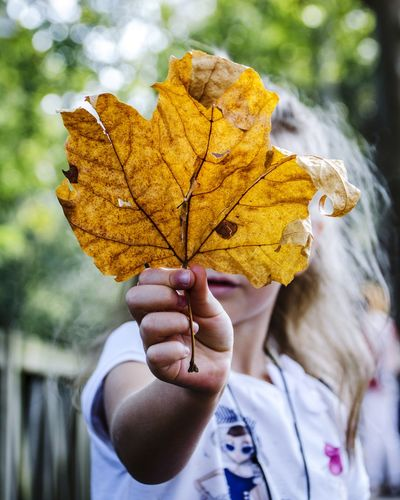 Girl holding maple leaf against face