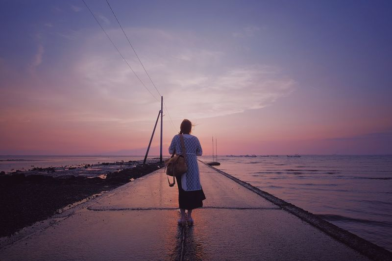 Rear view of woman standing on pier in sea against sky