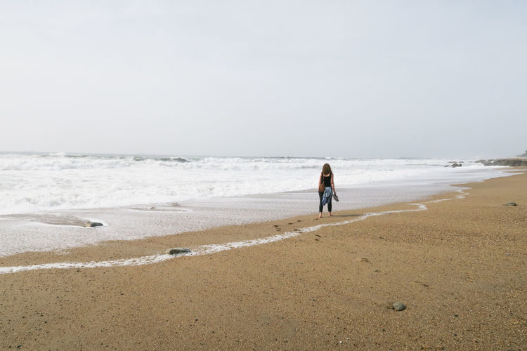 young women walking at the sand beach of the atlantic ocean in porto, portugal Young Women Porto Portugal Atlantic Ocean Seawater Febuary  Water Full Length Sea Beach Low Tide Sand Wave Summer Walking Rear View Analogue Sound