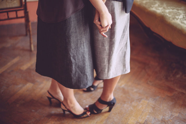 Low section of lesbian couple standing on wooden floor