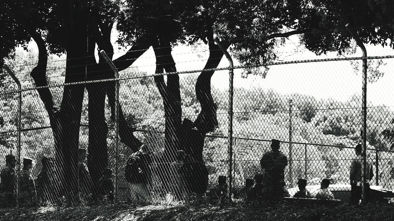 Rear View Of Army Soldiers Standing Behind Chainlink Fence